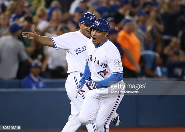 Ezequiel Carrera of the Toronto Blue Jays celebrates as he is congratulated by third base coach Luis Rivera after hitting a pinchhit solo home run in...