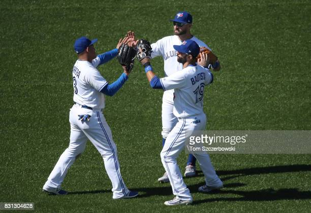 Ezequiel Carrera of the Toronto Blue Jays celebrates their victory with Kevin Pillar and Jose Bautista during MLB game action against the Pittsburgh...