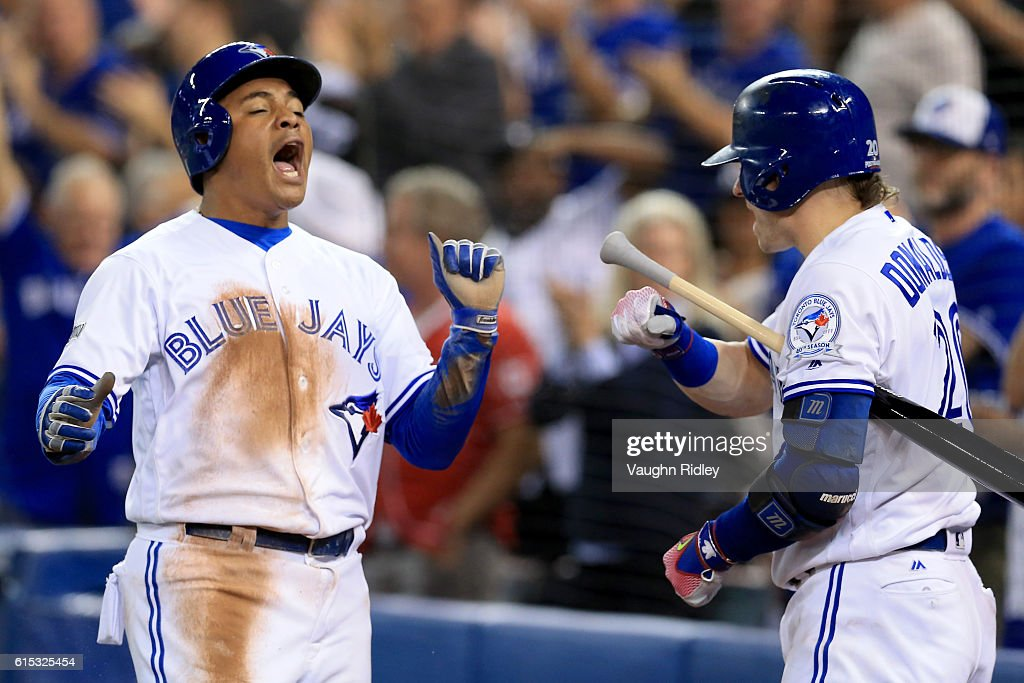 Ezequiel Carrera #3 of the Toronto Blue Jays celebrates with teammate Josh Donaldson #20 after scoring a run off of a grounded out single hit by Ryan Goins #17 in the fifth inning against the Cleveland Indians during game three of the American League Championship Series at Rogers Centre on October 17, 2016 in Toronto, Canada.