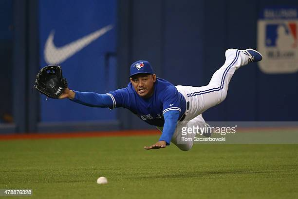 Ezequiel Carrera of the Toronto Blue Jays dives but cannot get to a single which he traps in the first inning during MLB game action hit by Rougned...