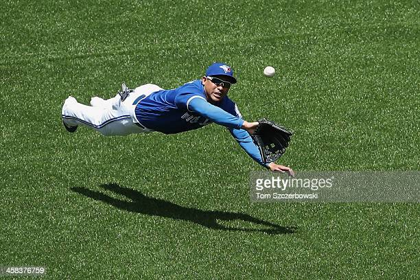 Ezequiel Carrera of the Toronto Blue Jays dives but cannot get to an RBI triple by Rajai Davis of the Cleveland Indians in the third inning during...
