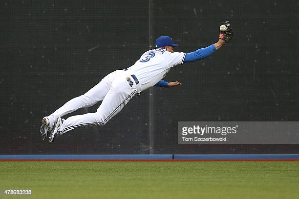 Ezequiel Carrera of the Toronto Blue Jays dives but cannot grab a single in the fourth inning during MLB game action hit by Mitch Moreland of the...