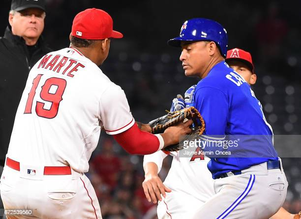 Ezequiel Carrera of the Toronto Blue Jays is tagged out in a run down play by Jefry Marte of the Los Angeles Angels in the eighth inning of the game...