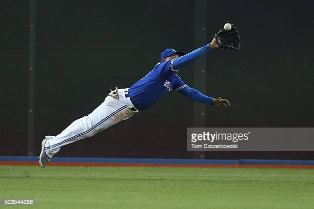 Ezequiel Carrera of the Toronto Blue Jays makes a diving catch in the ninth inning during MLB game action against the Oakland Athletics on April 23...