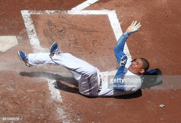 Ezequiel Carrera of the Toronto Blue Jays slides across home plate to score on a tworun double by Ryan Goins in the first inning during MLB game...