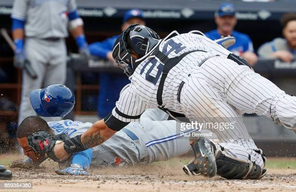 Ezequiel Carrera of the Toronto Blue Jays slides home safely on a sacrifice hit by Josh Donaldson as catcher Gary Sanchez of the New York Yankees...