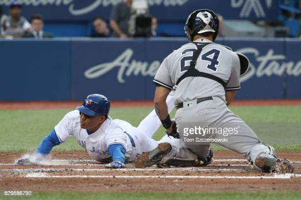 Ezequiel Carrera of the Toronto Blue Jays slides home safely to score a run in the second inning during MLB game action as Gary Sanchez of the New...