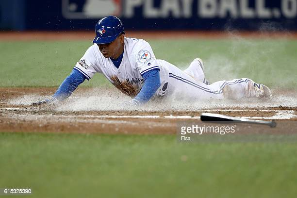 Ezequiel Carrera of the Toronto Blue Jays slides to home plate to score a run off of a grounded out single hit by Ryan Goins in the fifth inning...