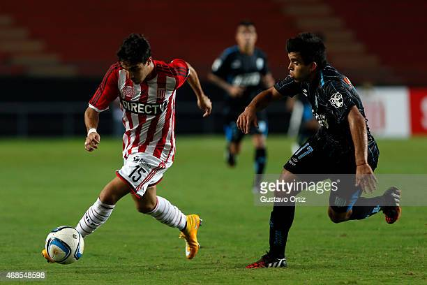 Ezequiel Cerutti of Estudiantes drives the ball as he is followed by Marcos Acuña of Racing during a match between Estudiantes and Racing Club as...