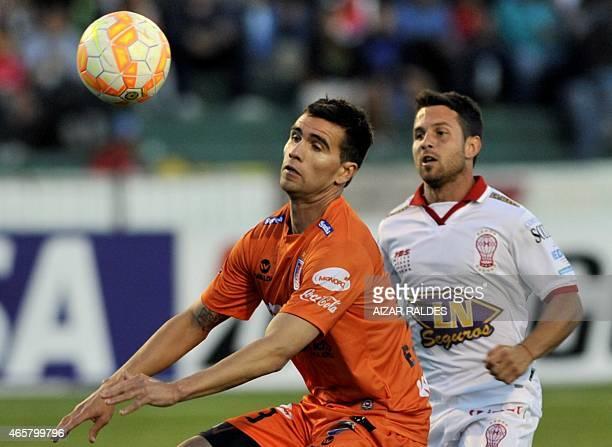 Ezequiel Filippeto of Bolivia's Universitario de Sucre and Agustin Torassa of Argentina's Huracan vie for the ball during their Libertadores Cup...