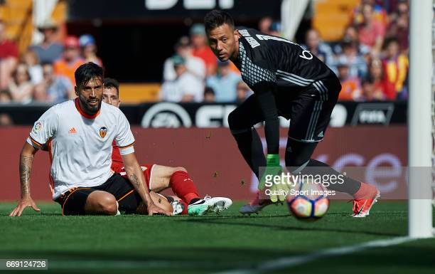 Ezequiel Garay and Diego Alves of Valencia competes for the ball with Stevan Jovetic of Sevilla during the La Liga match between Valencia CF and...