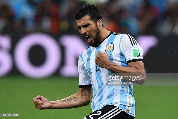 Ezequiel Garay of Argentina celebrates scoring his penalty kick during a shootout during the 2014 FIFA World Cup Brazil Semi Final match between the...
