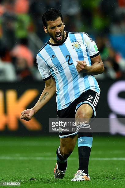 Ezequiel Garay of Argentina celebrates scoring in the penalty shootout during the 2014 FIFA World Cup Brazil Semi Final match between Netherlands and...