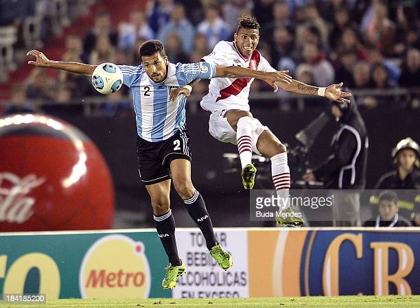 Ezequiel Garay of Argentina fights for the ball with Edwuin Gomez Gutierrez of Peru during a match between Argentina and Peru as part of the 17th...
