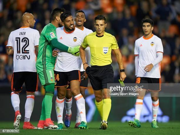 Ezequiel Garay of Valencia argues with the referee Del Cerro Grande during the La Liga match between Valencia CF and Real Sociedad de Futbol at...