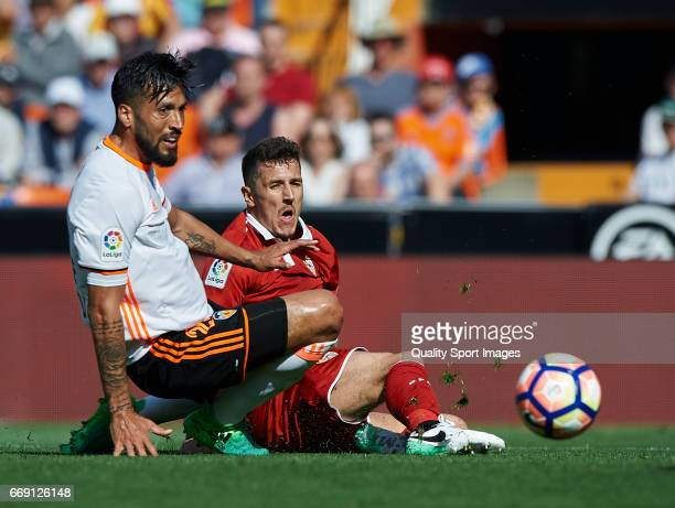 Ezequiel Garay of Valencia competes for the ball with Stevan Jovetic of Sevilla during the La Liga match between Valencia CF and Sevilla FC at...