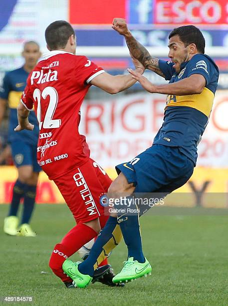 Ezequiel Ham of Argentinos Juniors is fouled and injured by Carlos Tevez of Boca Juniors during a match between Argentinos Juniors and Boca Juniors...