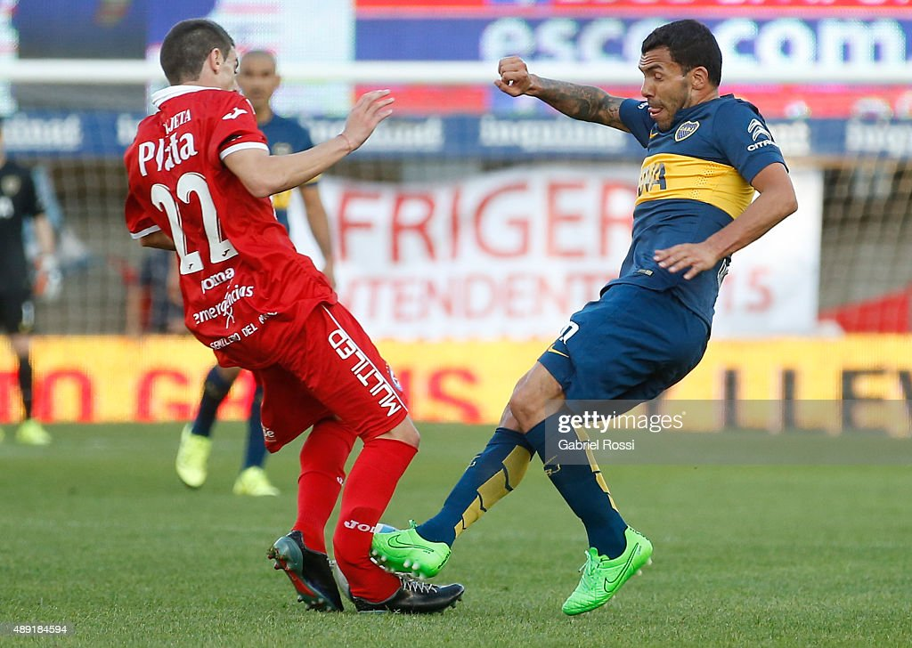 Ezequiel Ham of Argentinos Juniors is fouled and injured by <a gi-track='captionPersonalityLinkClicked' href=/galleries/search?phrase=Carlos+Tevez&family=editorial&specificpeople=220555 ng-click='$event.stopPropagation()'>Carlos Tevez</a> of Boca Juniors during a match between Argentinos Juniors and Boca Juniors as part of 25th round of Torneo Primera Division 2015 at Diego Armando Maradona Stadium on September 19, 2015 in Buenos Aires, Argentina.