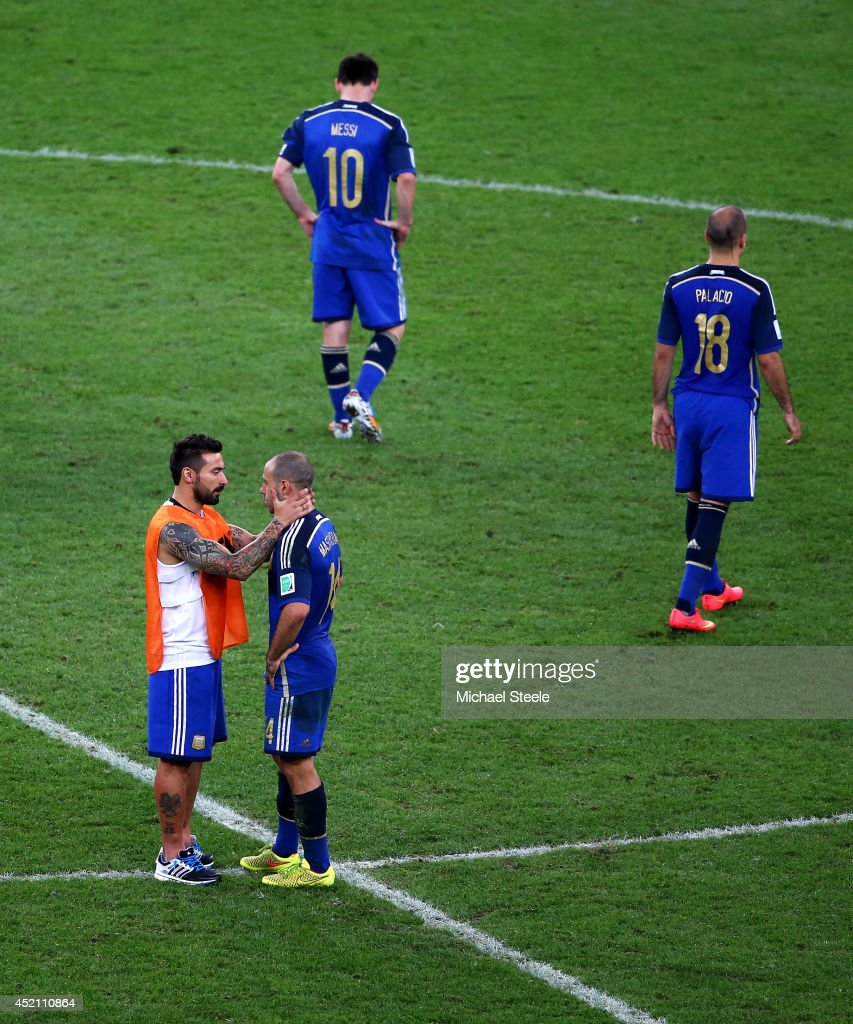 <a gi-track='captionPersonalityLinkClicked' href=/galleries/search?phrase=Ezequiel+Lavezzi&family=editorial&specificpeople=5451126 ng-click='$event.stopPropagation()'>Ezequiel Lavezzi</a> of Argentina consoles teammate <a gi-track='captionPersonalityLinkClicked' href=/galleries/search?phrase=Javier+Mascherano&family=editorial&specificpeople=490876 ng-click='$event.stopPropagation()'>Javier Mascherano</a> as <a gi-track='captionPersonalityLinkClicked' href=/galleries/search?phrase=Lionel+Messi&family=editorial&specificpeople=453305 ng-click='$event.stopPropagation()'>Lionel Messi</a> and <a gi-track='captionPersonalityLinkClicked' href=/galleries/search?phrase=Rodrigo+Palacio&family=editorial&specificpeople=490993 ng-click='$event.stopPropagation()'>Rodrigo Palacio</a> look on after being defeated by Germany 1-0 in extra time during the 2014 FIFA World Cup Brazil Final match between Germany and Argentina at Maracana on July 13, 2014 in Rio de Janeiro, Brazil.