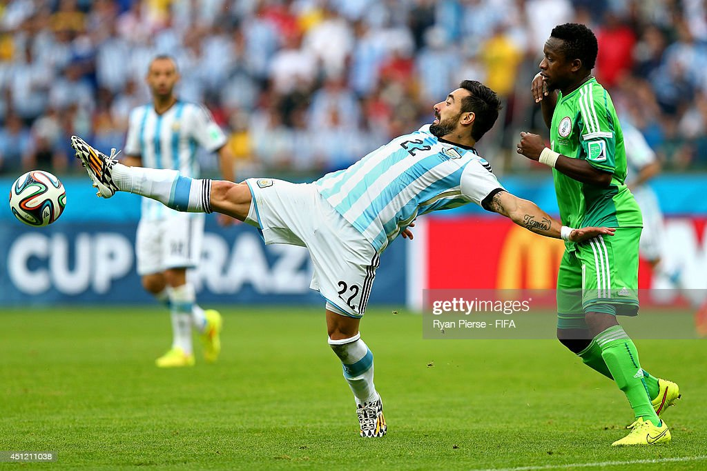 Ezequiel Lavezzi of Argentina holds off the challenge by Ogenyi Onazi of Nigeria during the 2014 FIFA World Cup Brazil Group F match between Nigeria...