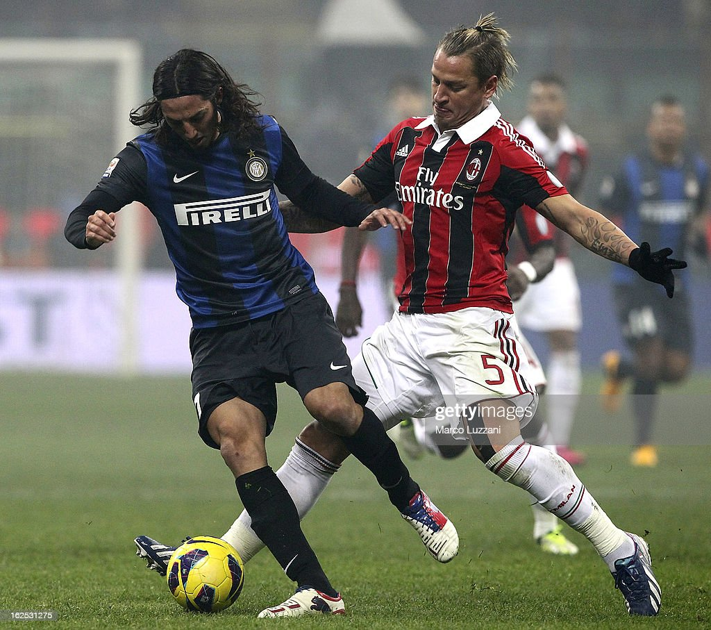 Ezequiel Matias Schelotto of FC Internazionale Milano competes for the ball with Philippe Mexes of AC Milan during the Serie A match FC Internazionale Milano and AC Milan at San Siro Stadium on February 24, 2013 in Milan, Italy.
