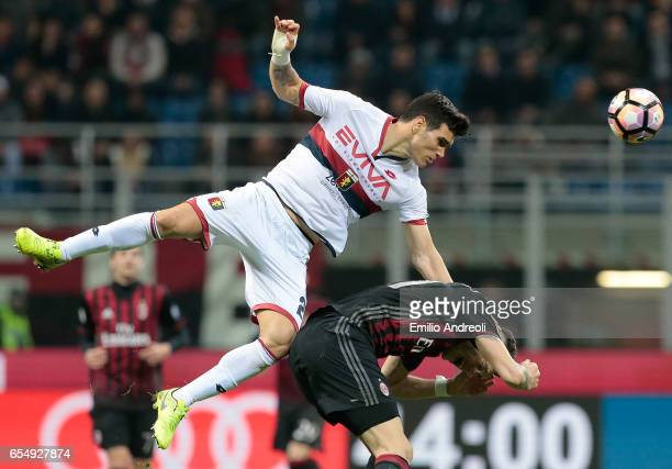 Ezequiel Munoz of Genoa CFC jumps for the ball with Lucas Ocampos of AC Milan during the Serie A match between AC Milan and Genoa CFC at Stadio...