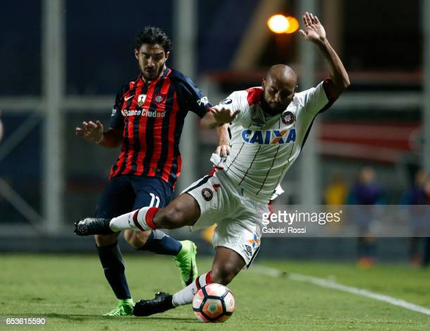 Ezequiel Osvaldo Cerutti of San Lorenzo fights for the ball with Jonathan of Atletico Paranaense during a group stage match between San Lorenzo and...