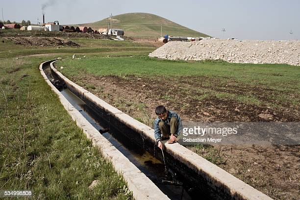 Ezidiar plays with an oil slick running through the agricultural land below the refinery Ezidiar a Yezidi boy from Sinjar lives with his displaced...