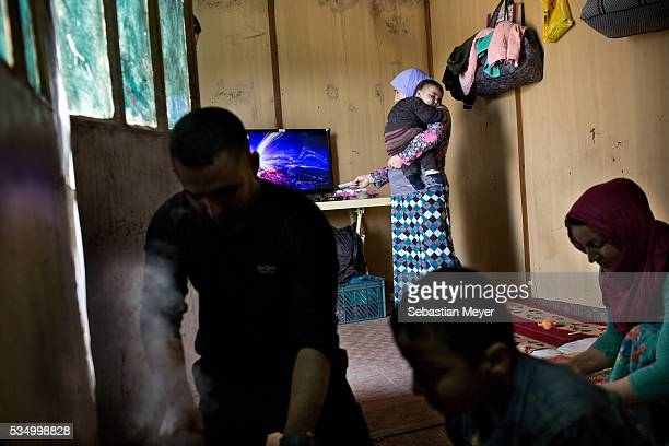 Ezidiar Zaydoon and his wife Hayam prepare lunch as Ghazal holds her grandson Mazal and changes the TV channel The family of Yezidis displaced from...