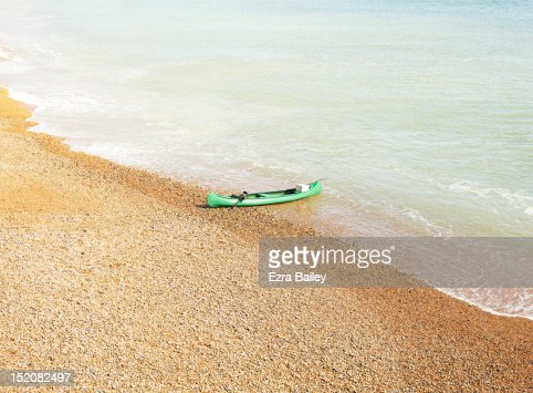 Green kayak on the beach : Stock Photo