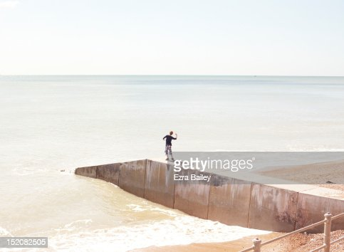 Boy throwing stone into ocean : Stock Photo
