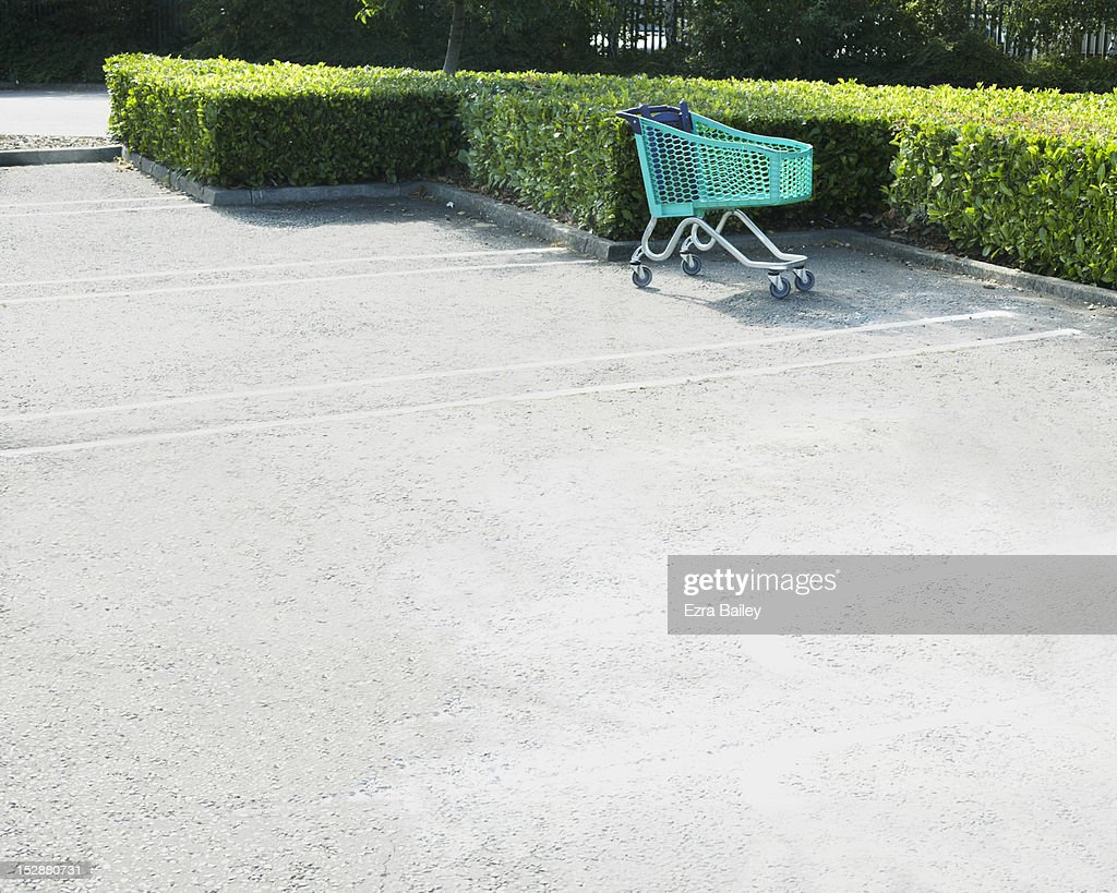 Empty green shopping trolly in empty car park : Stock Photo