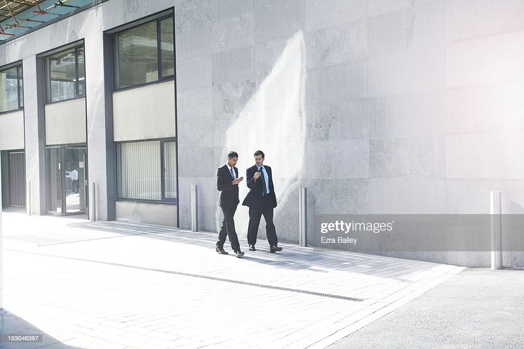 Two businessmen walking with their phones. : Stock Photo
