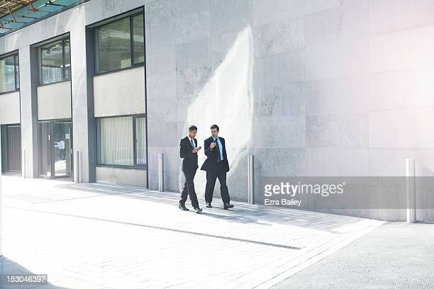 Two businessmen walking with their phones.