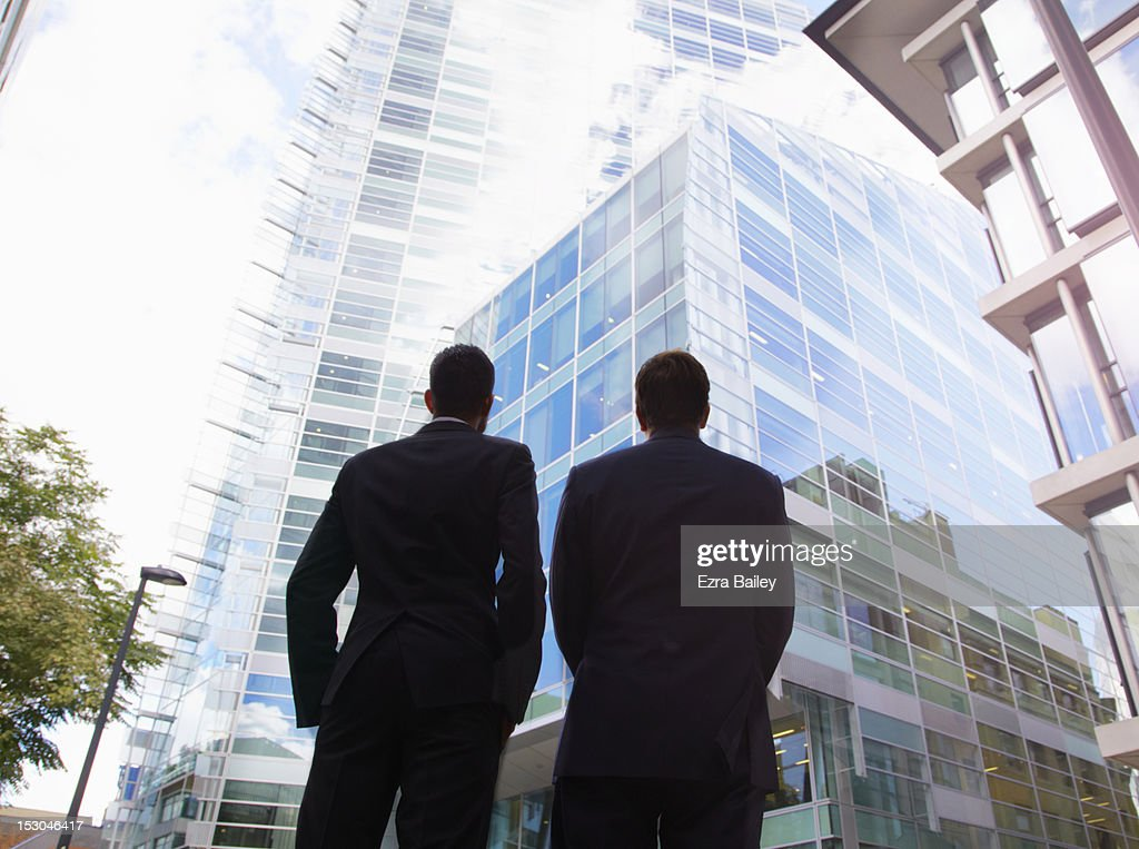 Two businessmen looking up at an office building : Stock Photo
