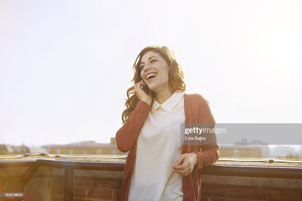 Woman on mobile phone on a roof top. : Stock Photo