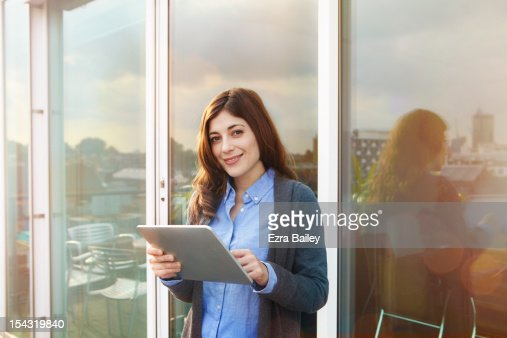 Young woman using digital tablet on roof terrace. : Stock Photo