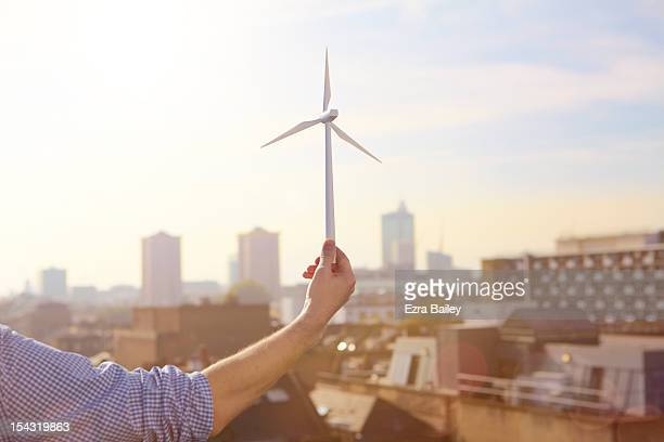 Man holding a model wind turbine.