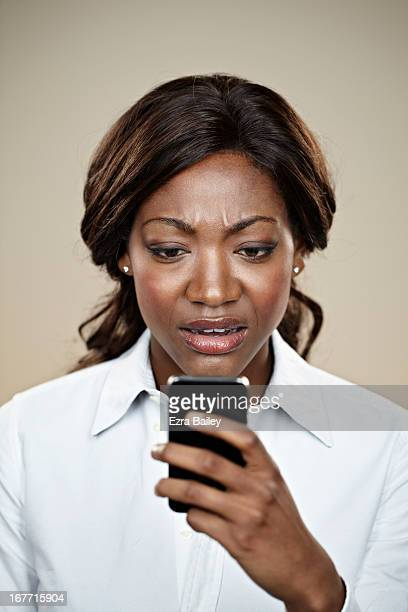 Female office worker looking at her mobile phone.