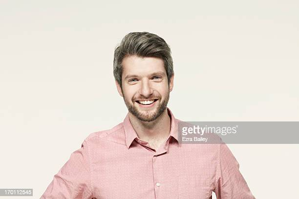 Man in a pink shirt smiling.