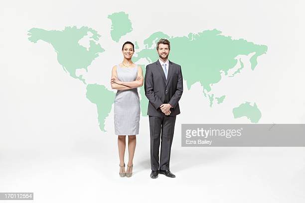 Businessman and woman standing with world map.