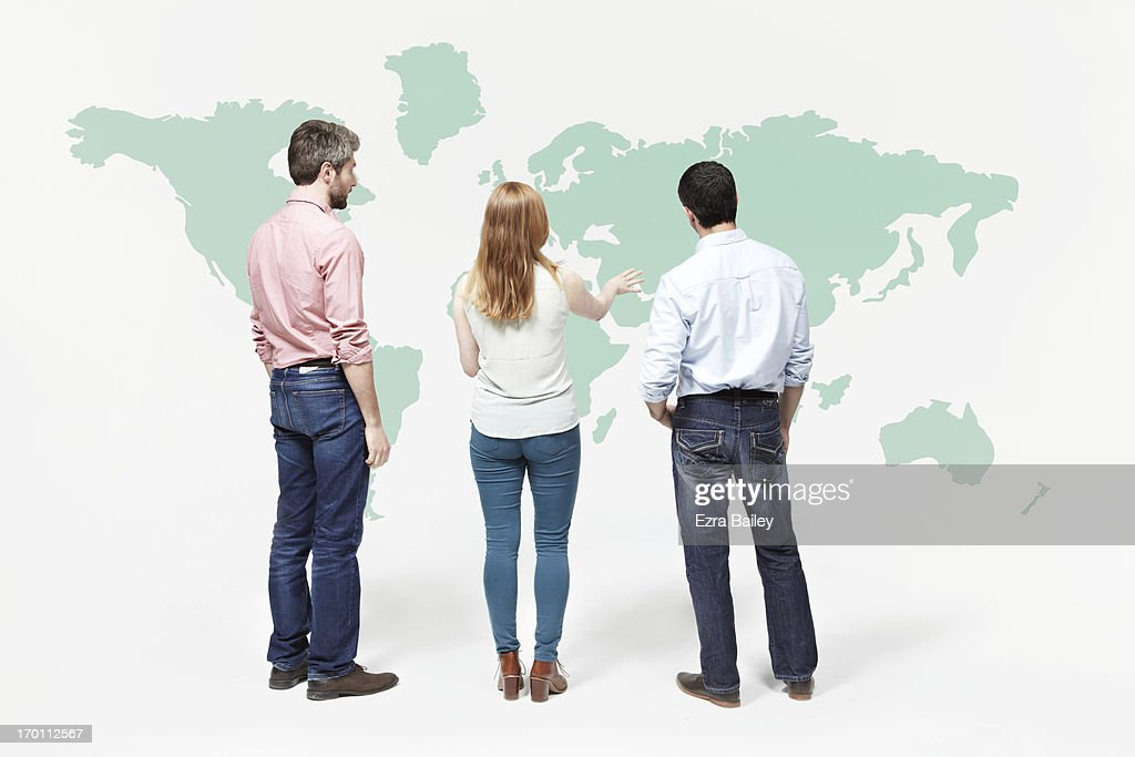 Group of people chatting in font of world map. : Stock Photo
