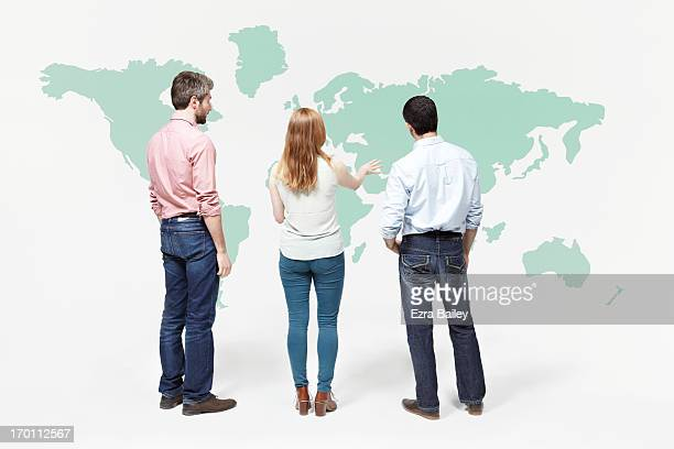 Group of people chatting in font of world map.