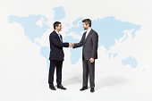 Businessmen shaking hands in front of world map