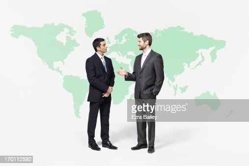 Businessmen chatting in front of world map. : Stock Photo
