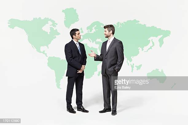 Businessmen chatting in front of world map.