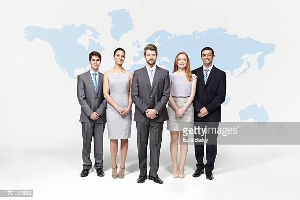 Group of business people standing with world map.