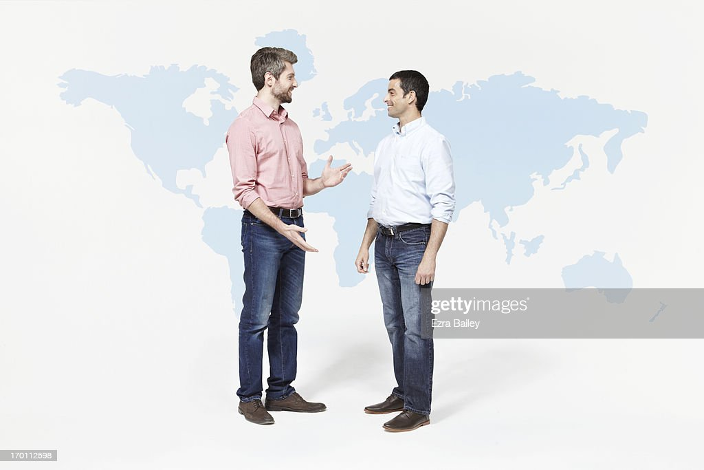 Two men chatting in front of world map. : Stock Photo