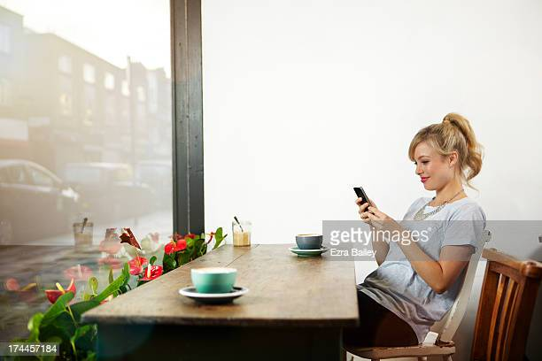 Woman using her mobile phone in a coffee shop.