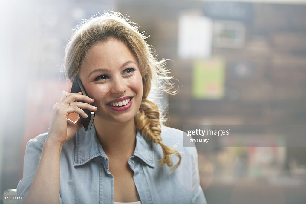 Woman on her mobile phone in a coffee shop : Stock Photo
